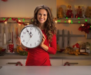Happy young housewife showing clock in christmas decorated kitchen